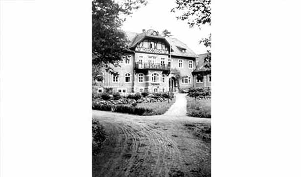 das schwarz-weiß Foto zeigt das Brunnenhaus, davor unbefestigte Wege