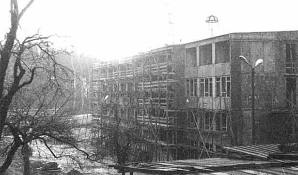 Blick auf die Baustelle, eingerüstete Fassade, Kran trägt Richtfestkrone