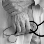 zwei Hände sind zu sehen, sie halten ein Stetoskop, die männliche Person trägt einen weißen Kittel, das Foto ist schwarz-weiß