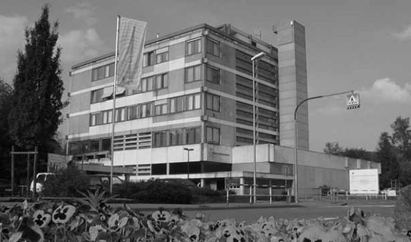 Blick auf das fünfstöckige Verwaltungsgebäude in Kork, davor wehen Fahnen und ein Fußgängerüberweg ist zu sehen, das Foto ist schwarz-weiß