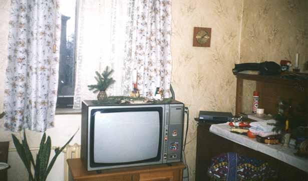 Blick in ein Zimmer, man sieht einen alten DDR-Fernsehen, ein Fenster mit Gardinen und eine Anrichte