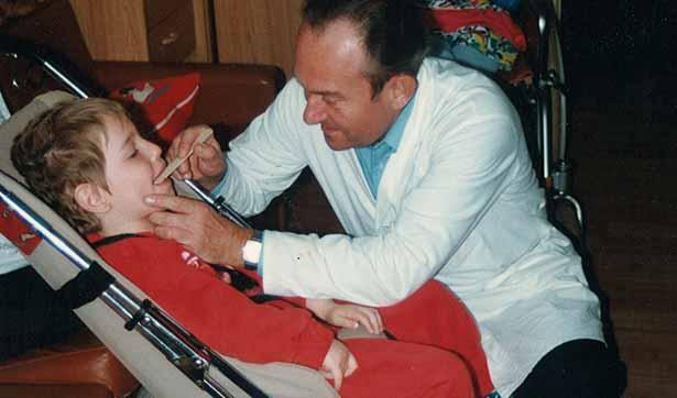 ein Arzt im weißen Kittel untersucht einen Jungen