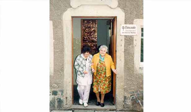 Eine Mitarbeiterin stützt eine ältere Bewohnerin beim Gang aus dem Haus