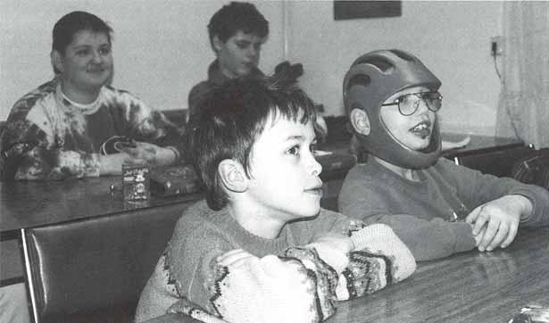 Vier Schüler sitzen im Klassenraum und folgen dem Unterricht