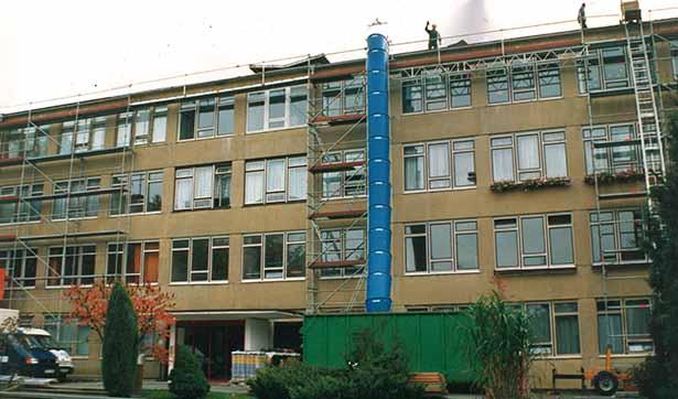 eingerüstetes Krankenhaus, zwei Bauarbeiter auf dem Dach
