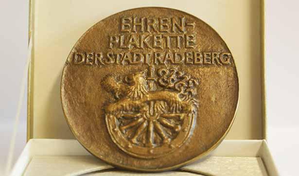 eine bronzene Plakette mit der Aufschrift Ehrenplakette der Stadt Radeberg, darunter das Wappen der Stadt, ein Löwe auf einem alten Holzrad
