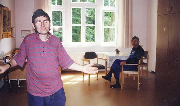 ein Bewohner des Talhauses öffnet die Tür und zeigt sein Zimmer