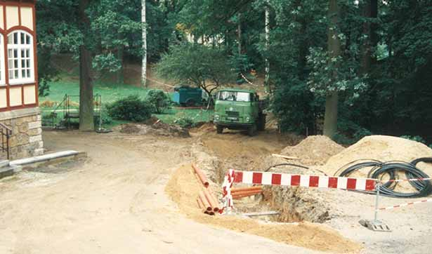 Erdarbeiten: ein offener Graben, viele Kabel, im Hintergrund ein LKW