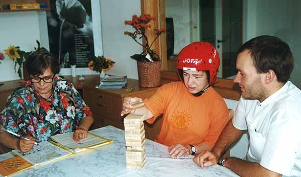 eine Patientin spielt mit Pfleger, eine andere Frau schreibt in einer Mappe