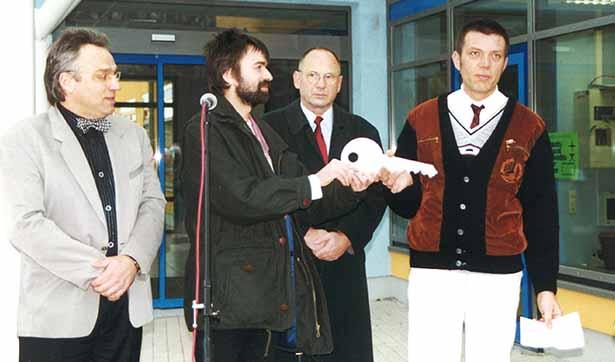 Vier Männer sind zu sehen, der Werkstattleiter bekommt einen großen symbolischen Schlüssel vom Bauleiter überreicht