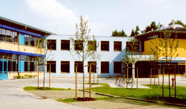 Blick auf drei Gebäude mit blau-gelber Fassade, davor eine große Freifläche