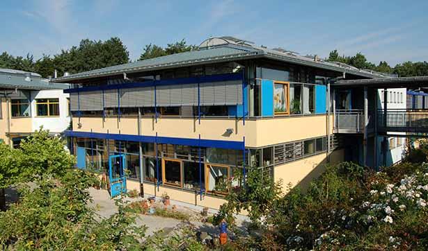 Blick auf die neue Werkstatt, große Fensterfront, gelb und blau gestaltete Fassade