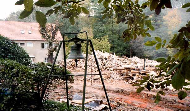 Abrissarbeiten der Tobiasmühle, ein Schutthaufen, davor steht eine Glocke