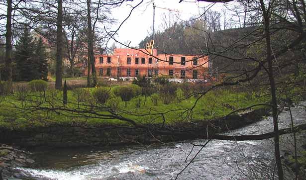 Blick auf die Baustelle der Tobiasmühle, davor fließt ein Fluss