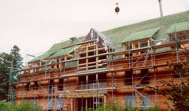 eingerüstetes Haus, die Richtfestkrone schwebt am Kran