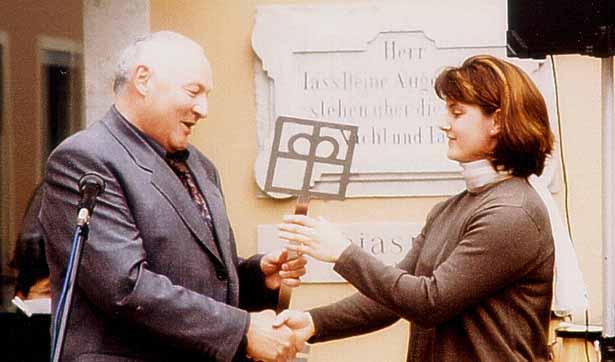 ein Mann übergibt einer Frau den symbolischen Schlüssel