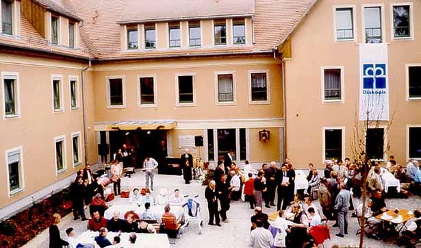 viele Menschen feiern die Einweihung auf dem Hof, dahinter stehen die neuen Gebäude