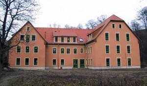 ein dreigeschössiges Gebäude mit einer rosa farbigen Fassade umringt von dichtem Wald