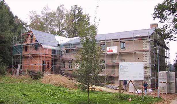 Blick auf die Baustelle, das Berghaus ist eingerüstet, ein Erweiterungsbau steht shon