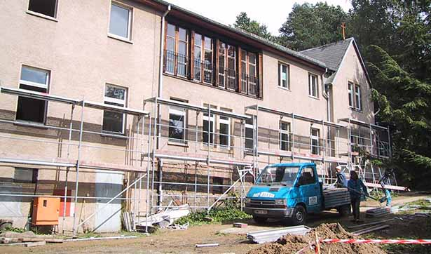 Blick auf die Baustelle, ein Auto steht vor der eingerüsteten Fassade