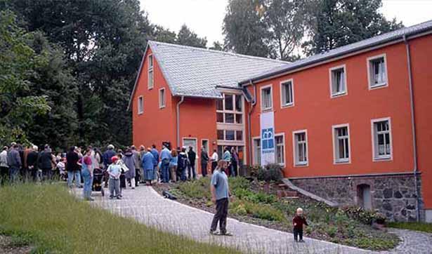 viele Menschen besichtigen das Haus, deutlich ist die rote Fassade zu erkennen