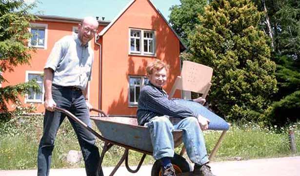 ein Bewohner sitzt in einer Schubkarre, diese schiebt der technische Leiter Jens Tetschke