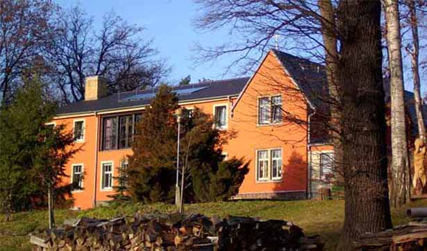 fertig gestelltes Berghaus, markant rote Fassade, dunkles Dach, davor einige Bäume