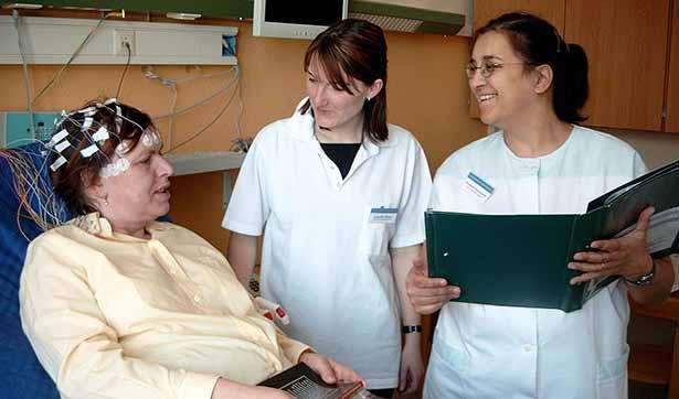 zwei Krankenschwestern stehen an dem Patientenbett, die Patientin ist an einem EEG angeschlossen