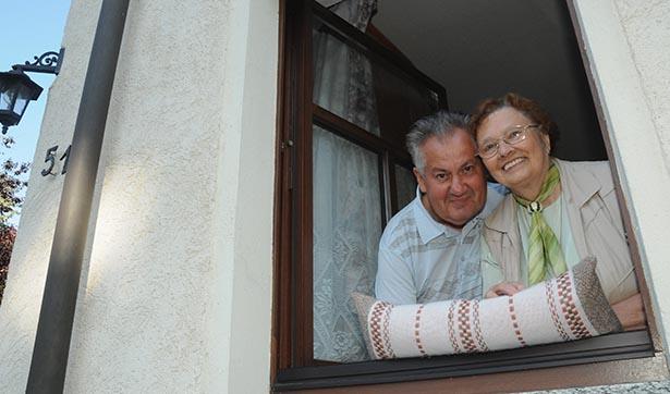 ein Mann und eine Fraue schauen aus dem Fenster, sie freuen sich sichtlich