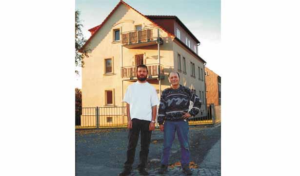 zwei Männer stehen vor dem dreigeschössigen Gebäude