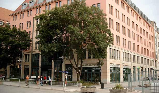 Blick auf das Gebäude, im Erdgeschoss große Fensterfronten, die oberen Etagen haben eine rosane Fassade