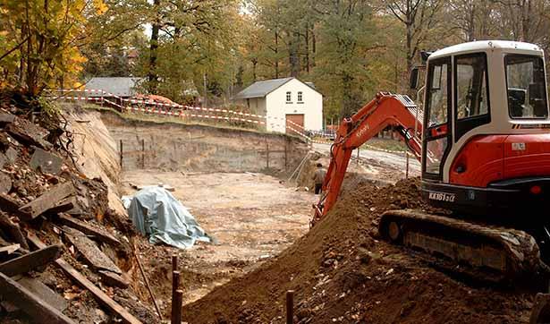 Blick auf die ausgehobene Grube, im Vordergrund steht ein kleiner Bagger
