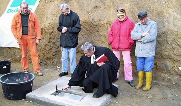 Pfarrer Wachsmuth lägt den Grundstein, er klopft mit einem Hammer auf die Platte, daneben stehen drei Bewohner und der Bauleiter