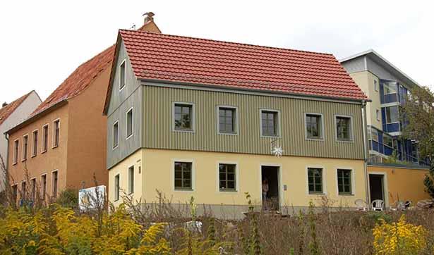 Blick auf das dreigeschössige Gebäude, mit gelber und grüner Fassade und einem roten Dach