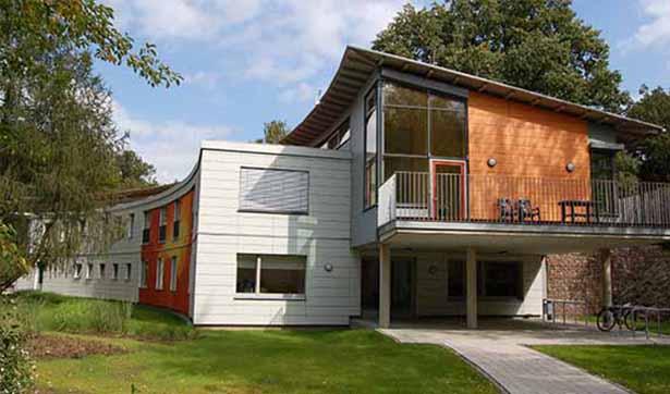 Blick auf das neue Gebäude in halbrunder Form, graue Fassade, moderne Architektur