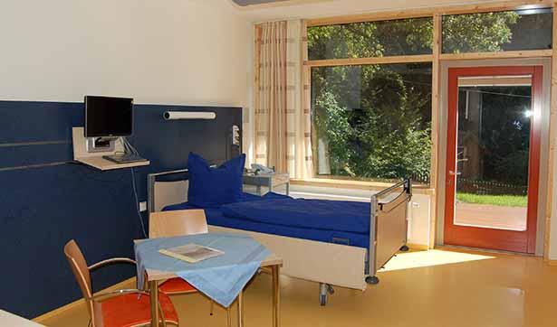 Ein helles, lichtdurchflutetes Zimmer mit einem Patientenbett und Tisch und Stühlen