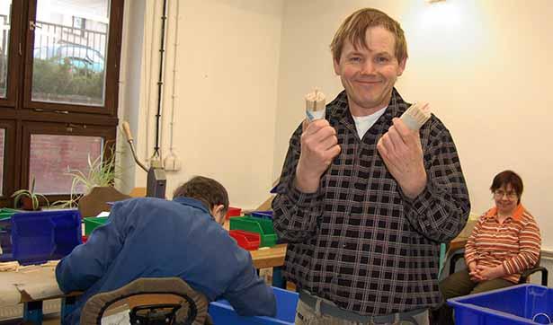 ein Beschäftigter hält 2 K-lumet Produkte in die Höhe