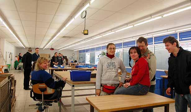 Blick in den Werkstattraum, mehrere Beschäftigte sitzen auf einem Tisch, im Hintergrund besichtigen Menschen die neuen Arbeitsplätze