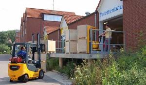 Blick auf die Verladerampe: ein Arbeiter bewegt die fertigen Paletten, ein Gabelstapler verteilt diese weiter