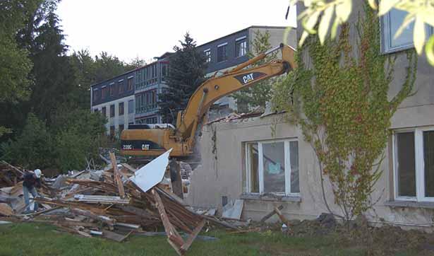 Ein Bagger reißt das Gebäude ein, im Hintergrund sieht man das Krankenhaus