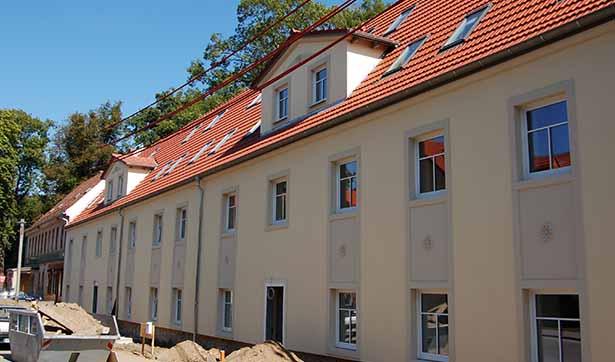 Blick auf einen modernisierten Altbau, hellgelbe Fassade mit Stuckelementen, rotes Dach, im Vodergrund werden noch die Wege gebaut
