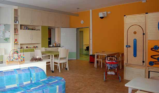 Aufenthaltsraum: im Vordergrund steht ein blaues Sofa, dahinter eine Sitzgruppe, kleine Tische und Stühle und auf der rechten Seite Spielzeug