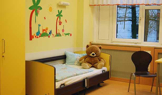 Blick in ein Zimmer der Kinderstation, auf einem Bett sitzt ein Plüschbär