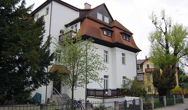 Eine Villa, weiße Fassade, rotes Dach, davor ein Eisenzaun