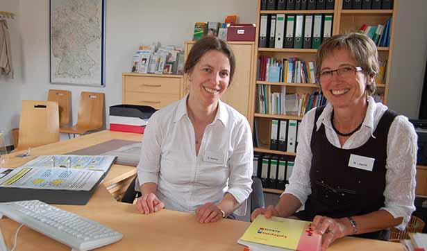 Zwei Beraterinnen lächeln in die Kamera, sie sitzen an einem Schreibtisch in der Beratungsstelle