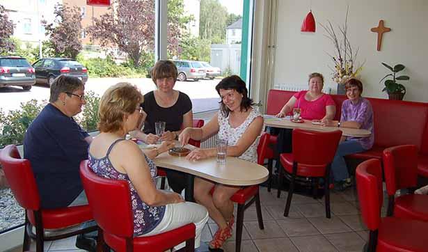 Blick in das Café, an zwei Tischen sitzen mehrere Personen