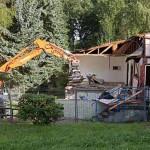 Ein Bagger reißt die Baracke ab, Bauzäune sperren das Areal ab