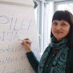 Dr. Polina Sediene steht vor einem Flipchart, auf das sie gerade EPILEPSIJA geschrieben hat, was litauisch für Epilepsie steht