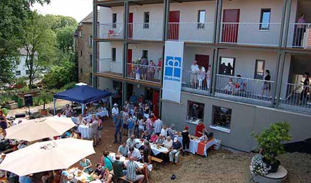 Blick von oben auf den Hinterhof, viele Menschen sind dort versammelt, an den Balkonen hängt eine Diakonie-Fahne