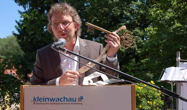 ein Mann steht vor einem Rednerpult, er hält einen symbolischen Schlüssel in die Höhe